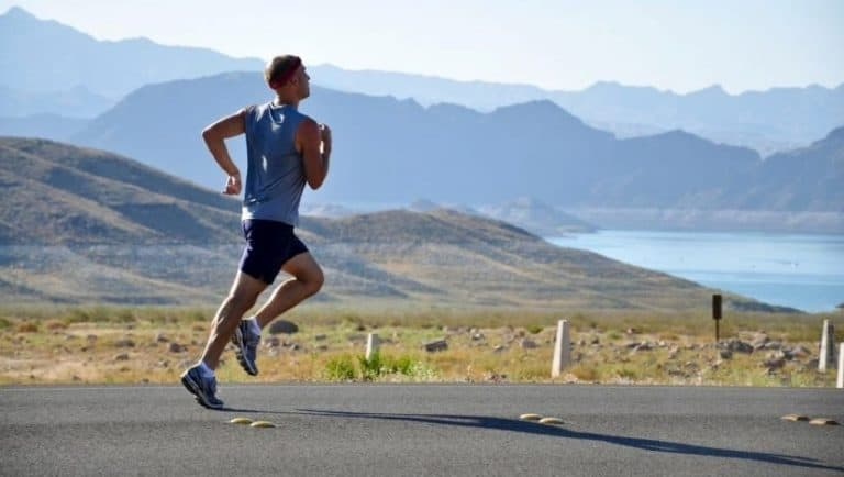 man in blue tank top, black shorts and running shoes outfit