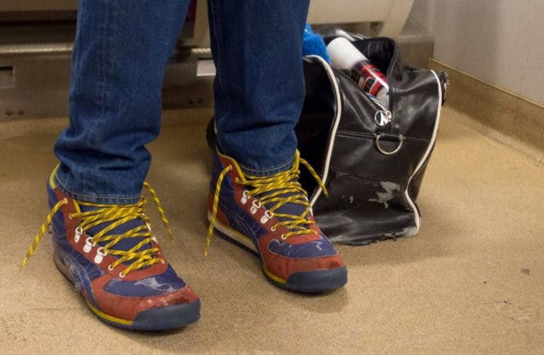 man`s legs with blue trousers and colorful sneakers with untied shoelaces