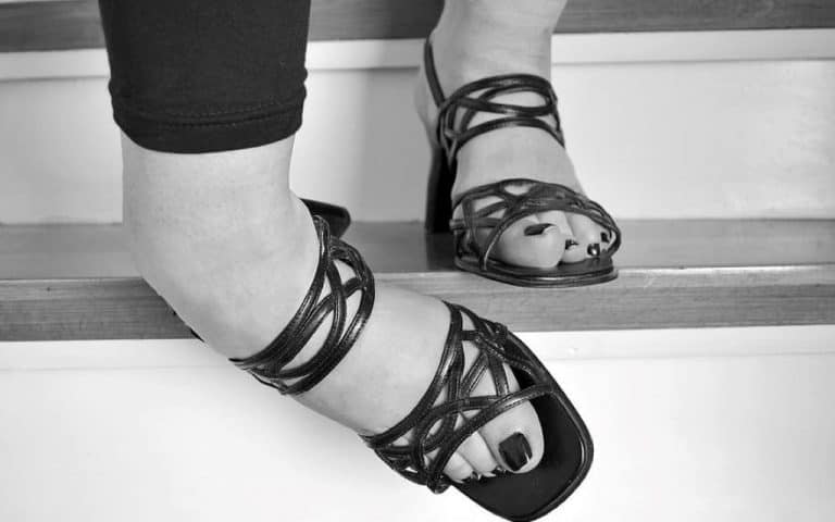 woman wearing heeled sandals walking on staircase
