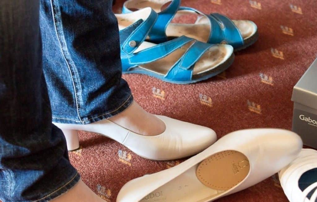 women fitting a white shoe and blue shoe