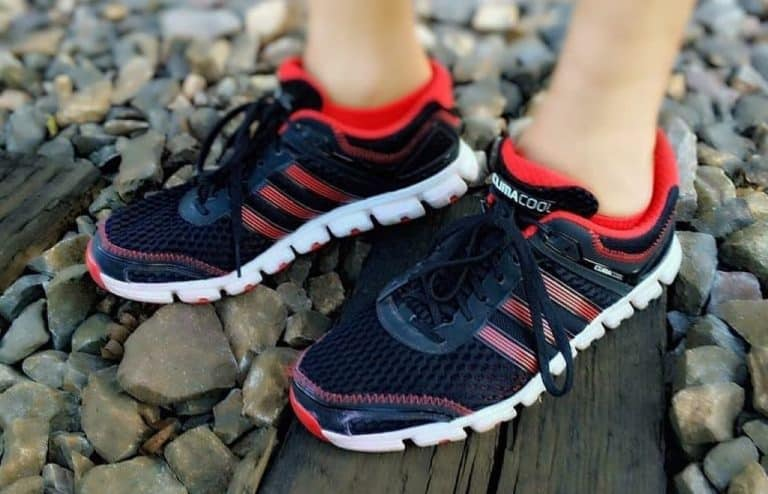Person wearing black red and white running shoes