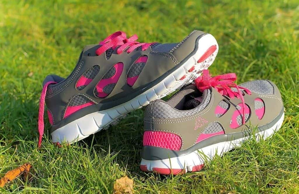 White and pink nike sneakers on green grass
