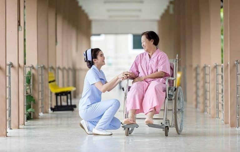 elderly woman on a wheelchair and nurse at the hospital