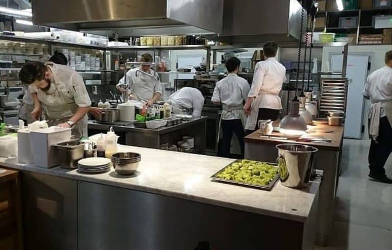 men cooking on commercial griddle and walking in the kitchen