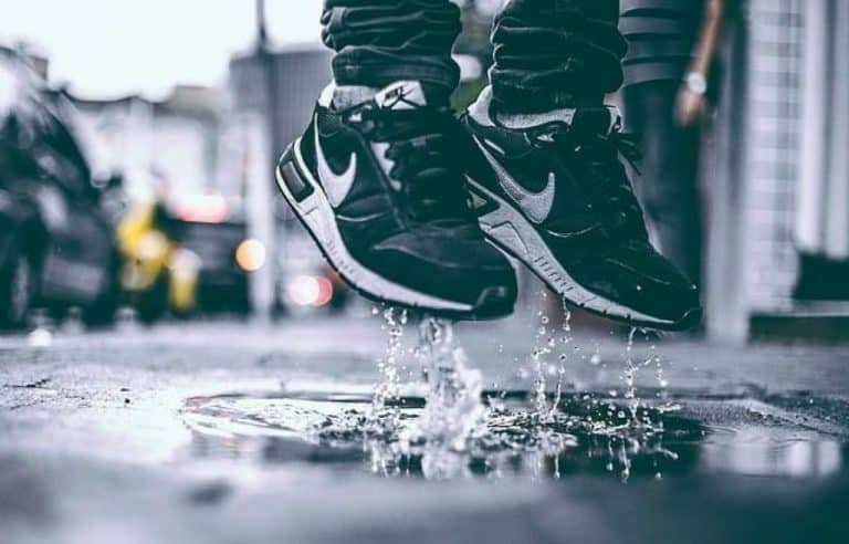person in pair black and white Nike running shoes