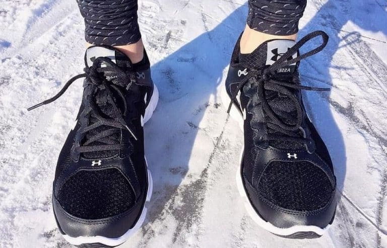 person running in the snow with winter footwear