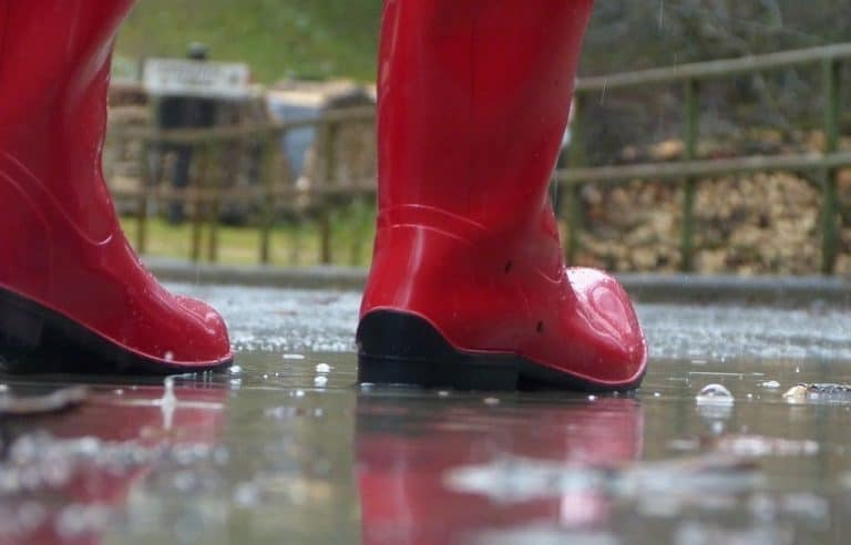 person wearing red boots raindrop rubberboots