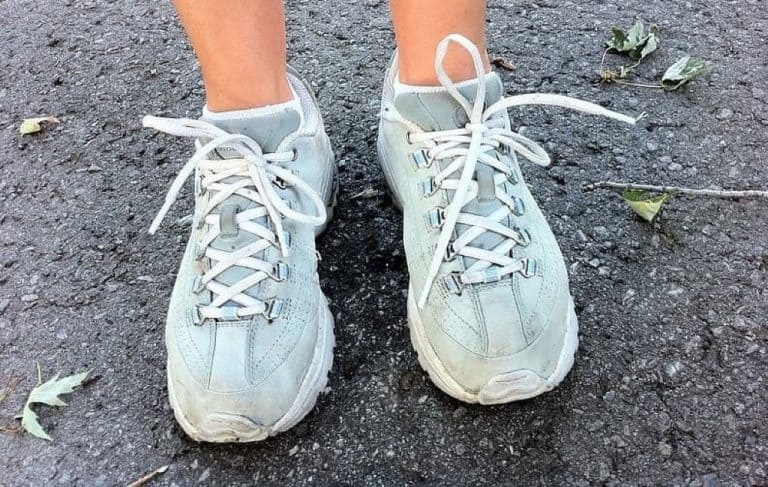 person's feet wearing blue and white running shoes