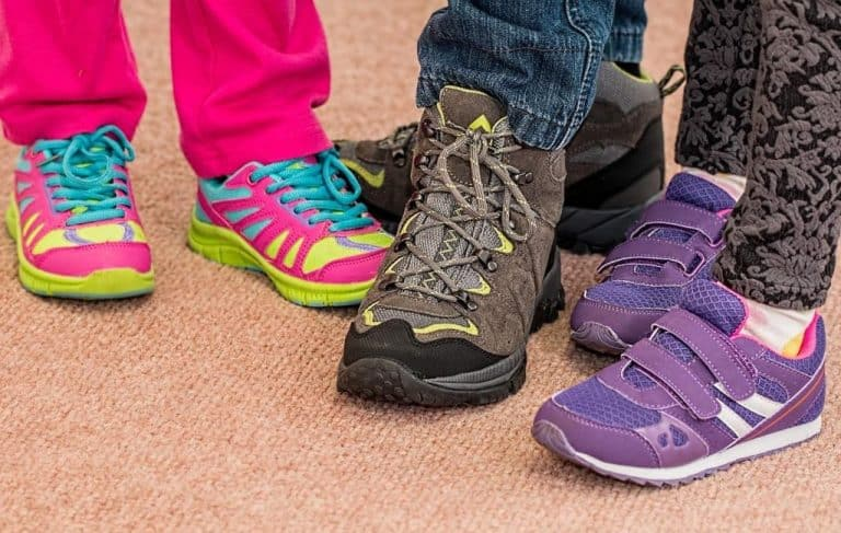 three kids showing off sports shoes
